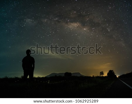 Scenery with the Milky Way The night sky with the stars and shadows of a young man standing alone.