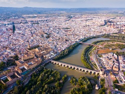 Scenic aerial view of ancient Roman bridge across Guadalquivir river and Moorish architecture of Mezquita-Catedral on background with Cordoba cityscape, Spain