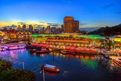 Scenic aerial view of Clarke Quay and Riverside area at blue hour in Singapore, Southeast Asia. Waterfront skyline reflected on Singapore River. Popular attraction for nightlife.