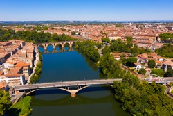 Scenic aerial view of French commune of Montauban on sunny summer day looking out over arched Old Bridge across Tarn river..