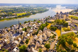 Scenic aerial view of Saumur town on banks of Loire in western France overlooking ancient castle and parish church in summer..
