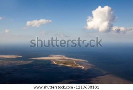 scenic aerial view of the uninhabited German island Minsener Oog in the North Sea under a vivid blue sky with white clouds and surrounded by deep blue water while low tide #1219638181