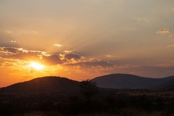 Scenic African Bushveld sunset with burning orange sun peeking from behind the clouds sending the suns rays into the horizon