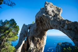 Scenic afternoon view through the Arco Naturale natural stone arch in the dramatic landscape of the Mediterranean island of Capri, Italy