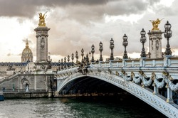 Scenic Alexander III bridge with ornate light posts and Dome des Invalides cathedral in a distance, Paris, France