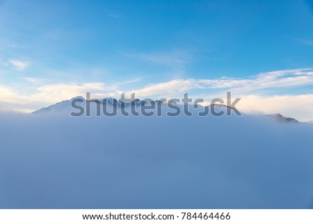 Scenic alpine landscape, clouds on the valley arisign mountain peaks sunset light, winter snow. #784464466