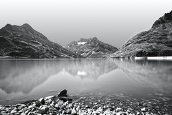Scenic alpine landscape with lake and mountains. Reflections in a calm mountain lake. Monochrome, black and white photography.