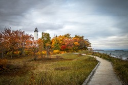 Scenic Autumn Lighthouse Landscape. Winding boardwalk path through dune grass along Lake Superior with vibrant autumn colors framing the Point Iroquois Lighthouse in the Upper Peninsula of Michigan.