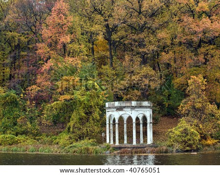 Scenic autumn view of old, weathered gazebo along a lake.