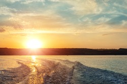 Scenic bright vibrant blue to red warm sunset evening time landscape with motorbaot swirl trace on water surface of lake or river. Horizon coast line on background