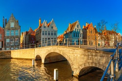 Scenic city view of Bruges canal with beautiful medieval colored houses and sunny bridge in the morning, golden hour, Belgium
