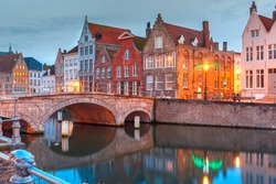 Scenic city view of Bruges canal with beautiful medieval colored houses, bridge and reflections, Belgium