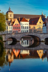 Scenic city view of Bruges canal with beautiful medieval colored houses, bridge and reflections in the evening gold hour, Belgium