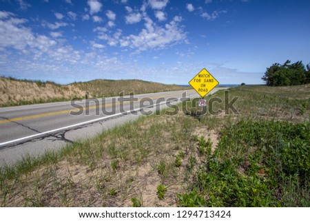 Scenic Coastal Highway. Coastal Highway along the shores of Lake Michigan surrounded by sand dunes with sign warning of sand on roadway in the Upper Peninsula of Michigan. #1294713424