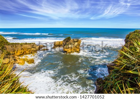 """Scenic coastline, powerful surf, huge stones and rocks. Stone flat """"pancakes"""". Pancake Rock is a natural wonder of Paparoa National Park, New Zealand. The concept of ecological, active  tourism"""