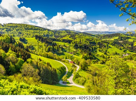 Scenic countryside landscape: green summer mountain valley with forests, fields and old houses in Germany, Black Forest