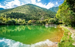 Scenic crescent moon lake pool view with Cangshan mountain water reflection in the Butterfly spring park in Dali Yunnan China
