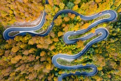 Scenic curvy road seen from a drone in autumn.
