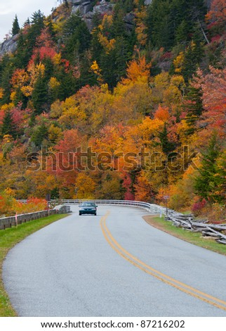 Scenic drive. A car, surrounded by colorful fall foliage,  travels the scenic Blue Ridge Parkway, North Carolina.