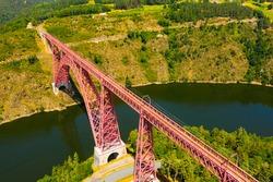 Scenic drone view of parabolic arched framework of railway bridge Viaduc de Garabit across river Truyere near Ruynes-en-Margeride in Auvergne, France..