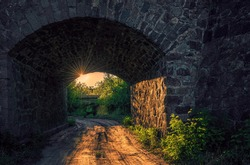 Scenic evening rural landscape in Wales. The arch of an old stone bridge and a dirt road against the backdrop of a summer green forest and the setting sun. Ecotourism and hiking in the UK