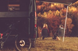 Scenic Fall Foliage RV Camper Camping. Caucasian Couple Seating Next to Their Motorhome and Enjoying the Scenery. Campsite Pitch.