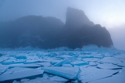 Scenic field of graphical cracked figured ice floes and mountain rock in fog on background, mystic winter morning landscape