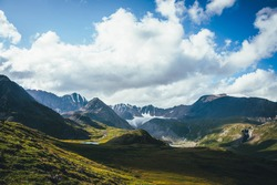 Scenic green blue alpine landscape with mountain lake in highland valley in sunlight and big glacier under cloudy sky. Shadow of clouds on green mountain valley. Clouds shadow on rocks and hills.