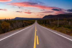 Scenic highway during a vibrant sunny day in the fall season. Dramatic Sunset Sky Art Render. Taken in Newfoundland, Canada.