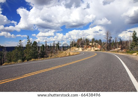 Scenic highway through Bryce National Park with dramatic cumulus cloud cloudscape against blue sky overhead