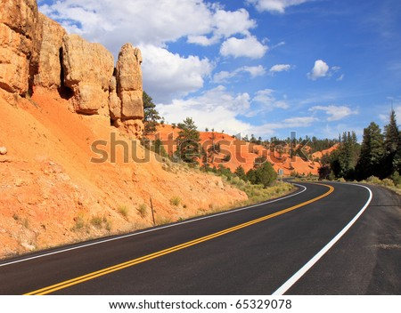 Scenic highway winds through red sandstone spires in Red Canyon, near Bryce National Park