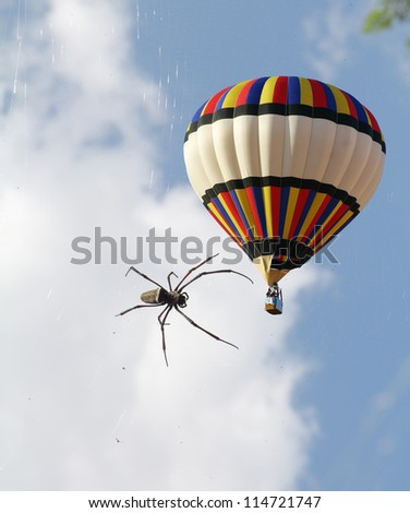 Scenic hot air balloon in free flight and a big spider. Sunny April day in the south
