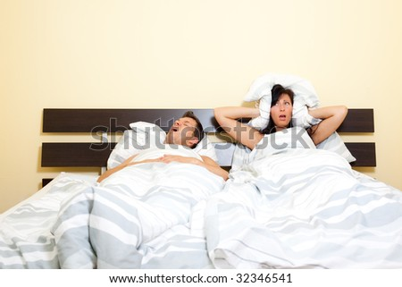 Scenic in bedroom of pair of loving with young couple lying in bed and holding pillow on the ears because of snoring boyfriend.