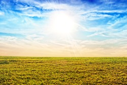 Scenic landscape background of blue sky and faded meadow grass in late autumn. Wide view of rural scenery. Nature wallpaper
