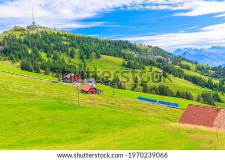 Scenic landscape between Alps, valleys of Rigi Mountain railways and blue cog train. Rigi Kulm summit and telecommunications tower on background. Canton of Schwyz and Lucerne, Central Switzerland. Stock fotó ©
