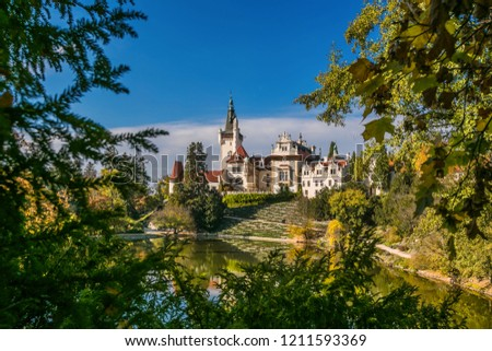 Scenic landscape of famous romantic Pruhonice castle, Czech Republic, Europe, standing on hill in a park, sunny colorful fall day, blue sky, spruce branches and maple leaves framing picture