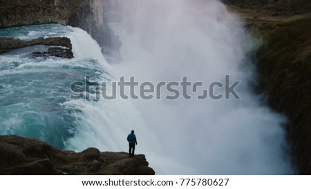 Stock Photo Scenic landscape of the lonely man standing on the edge of the mountain and looking on the Gullfoss waterfall in Iceland
