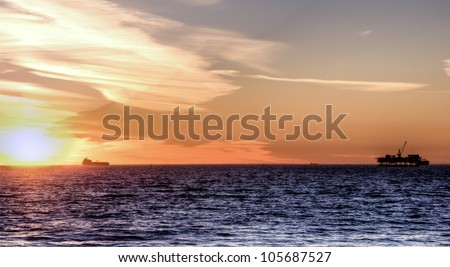 Scenic landscape off shore oil rig and cargo ship at sunset