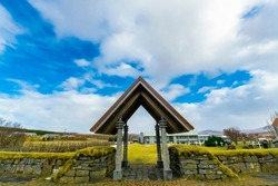 Scenic landscape shot capturing an entrance gate to a beautiful garden with a cemetery on the side. Overcast cloudy sky with green grass & blue skies adds magic and drama to this Icelandic nature shot