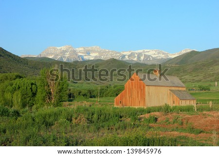 Scenic landscape with a wooden barn and Mt. Timpanogos, Utah, USA.