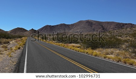 Scenic Long desert road ahead of Death Valley National Park, California