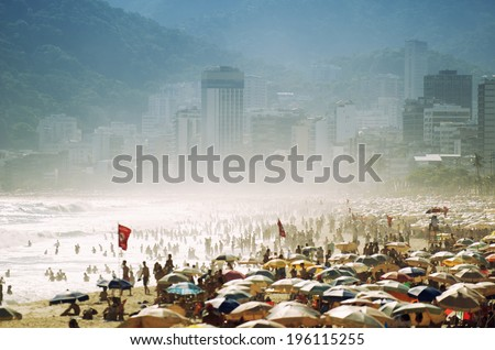 Scenic misty view of a busy day on Ipanema Beach with umbrellas and people crowding the shore in Rio de Janeiro, Brazil