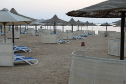 Scenic morning view. Luxury beach with deck chair in the evening time. Beautiful landscape Red Sea coast. Comfortable beach with lounge chairs under natural wooden umbrella with wind protection.