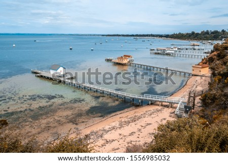 Scenic Mornington Peninsula coastline with beautiful wooden piers and sheds. Sorrento, Victoria, Australia #1556985032