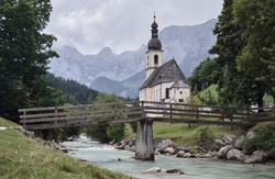 Scenic mountain landscape in the Bavarian Alps with famous Parish Church of St. Sebastian and creek with wooden bridge in the village of Ramsau near Berchtesgaden, Bavaria, Germany.