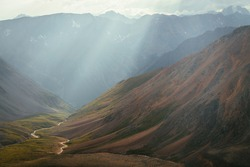 Scenic mountain landscape of motley mountain valley with river in sun rays. Wonderful highland scenery of multicolor valley with mountain river and red slope in sunbeams. Unusual fantasy minimalism.