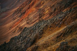 Scenic nature background of multicolor mountain. Colorful nature backdrop of motley rocks. Multicolor great rocks of vivid colors. Beautiful red orange rufous golden rocks. Closeup of motley mountain.