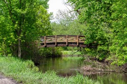 Scenic nature view of a rustic wooden bridge over a wooded rural river