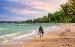 Scenic Neil Island seashore Andaman India at sunset with young tourist couple enjoy a walk along the beach