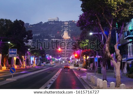 Scenic night view of the bahai temple and bahai gardens from the central street in Haifa, Israel. Deserted night road and red traffic light at background of beautiful slope of Mount Carmel